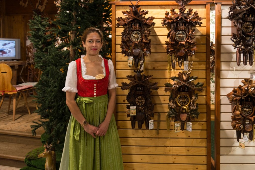 Girl dressed in dirndl in a cuckoo clock shop